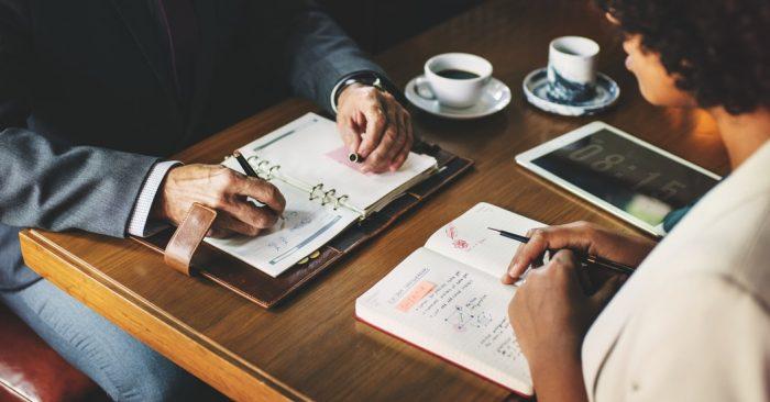 Empresários escrevendo no caderno